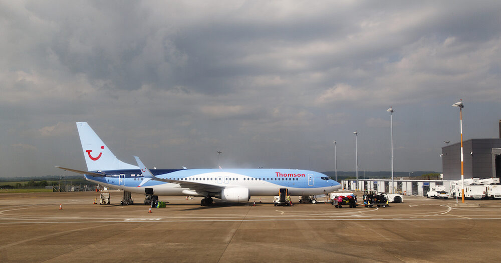 Cardiff, UK: : A Thomson Holidays airplane awaiting baggage loading at Cardiff Airport. Thomson are a UK based holiday travel operator.