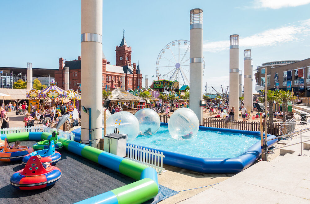 Cardiff United Kingdom - Children and families are enjoying zorb balls bumper cars and other activities at Cardiff Bay Beach fair at Roald Dahl Plass in Cardiff Bay Cardiff.