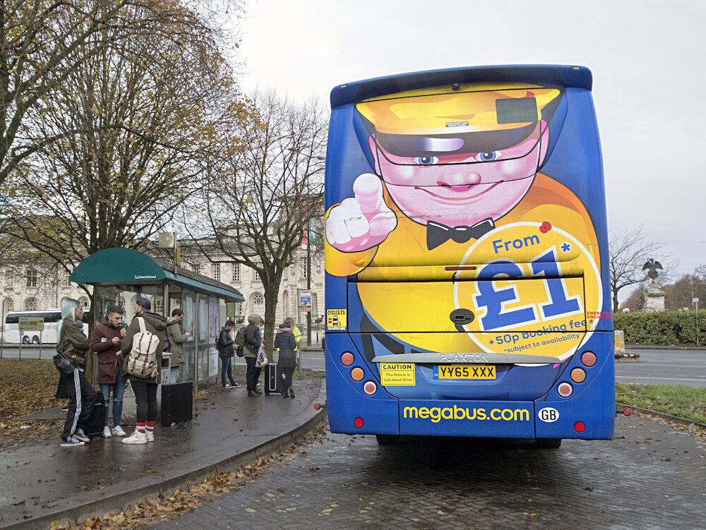 Cardiff, UK: Passengers wait at a bus stop. Megabus coach service travels to over 90 intercity destinations across the UK with cheap coach tickets from as little as £1.