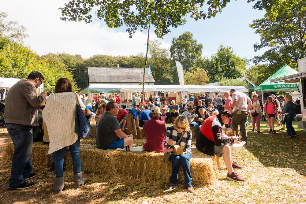 St Fagans, United Kingdom People sit eating on hay at the Food Festival in St Fagans, Cardiff, Wales