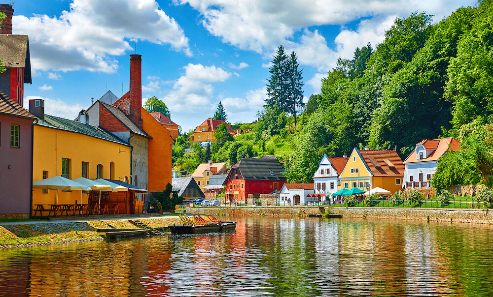 Cesky Krumlov (Czech Krumlov), Czech Republic. Antique town on river Vltava. Picturesque landscape with cosy colourful houses on banks among green trees. Sunny summer day with blue sky and clouds.