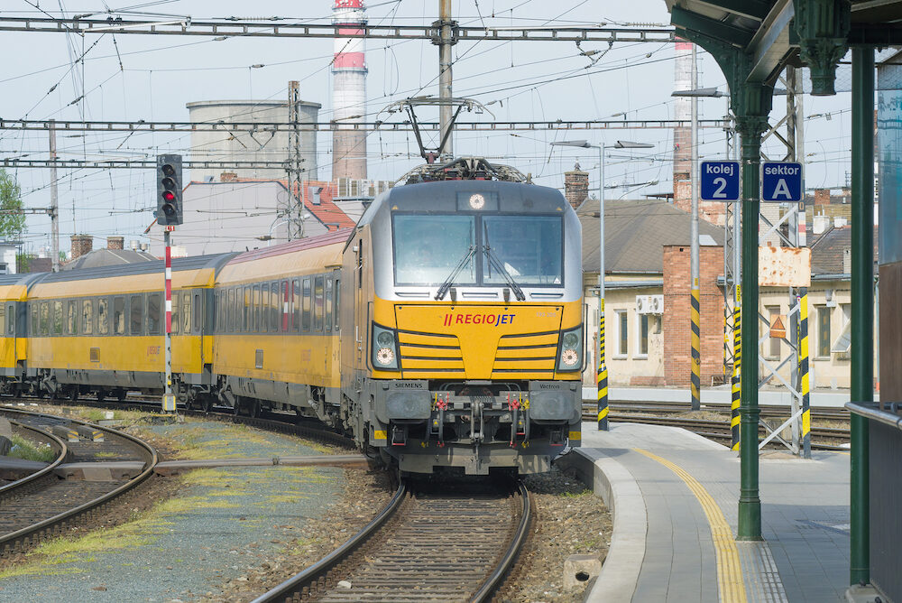 BRNO, CZECH REPUBLIC - The yellow passenger train of the RegioJet company arrives to the railway station of the city of Brno