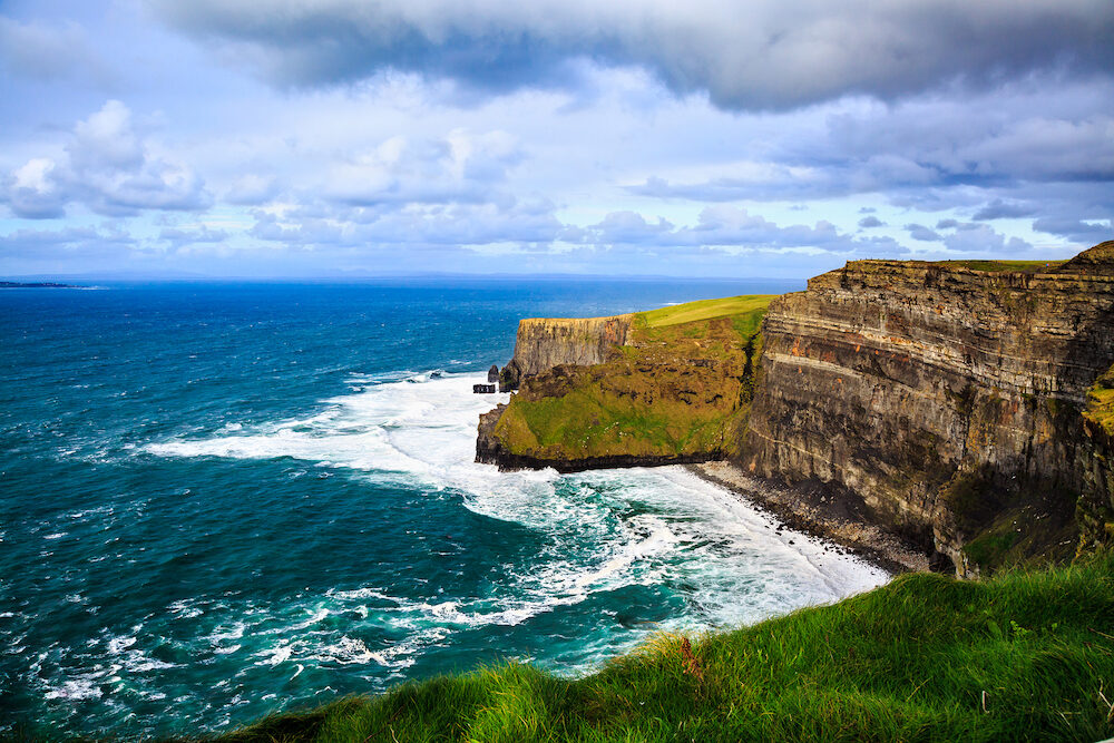 Cliffs of Moher, Burren, County Clare, Ireland. Sea cliffs rise above Atlantic Ocean. View from top cliffs in Galway Bay. Popular tourist attraction. Scenic seascape. Irish rural countryside nature.