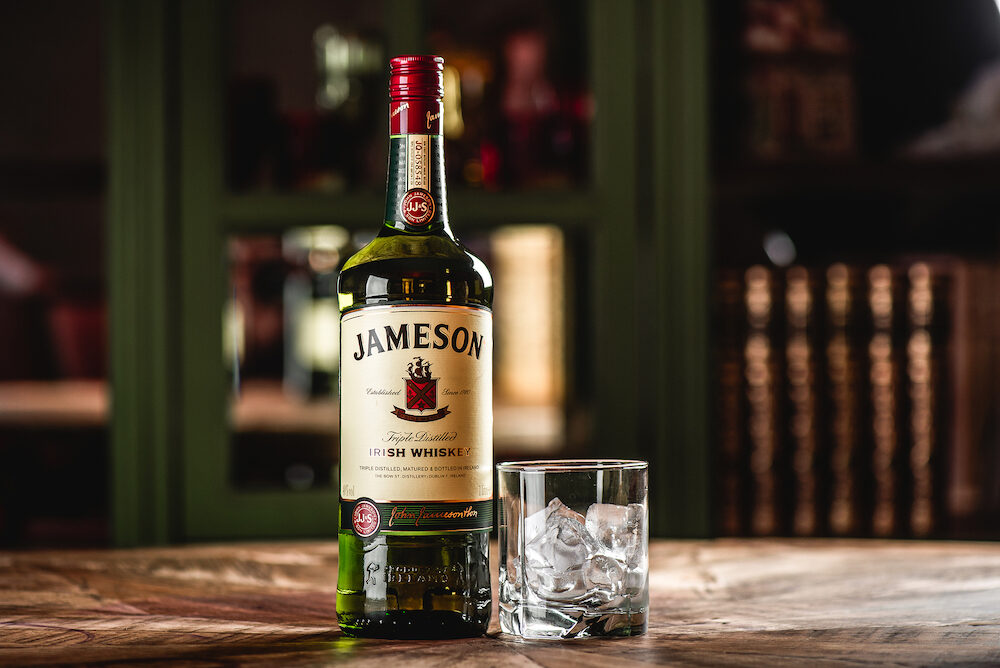 Moscow, Russia - Jameson whiskey bottle and glass with ice cubes on wooden table in dark bar. Jameson is a brand of traditional Irish whiskey from Dublin