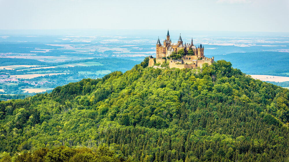Hohenzollern Castle on mountain top, Germany. This castle is a famous landmark in vicinity of Stuttgart. Scenic panorama of Burg Hohenzollern in summer. Landscape of Swabian Alps with Gothic castle.