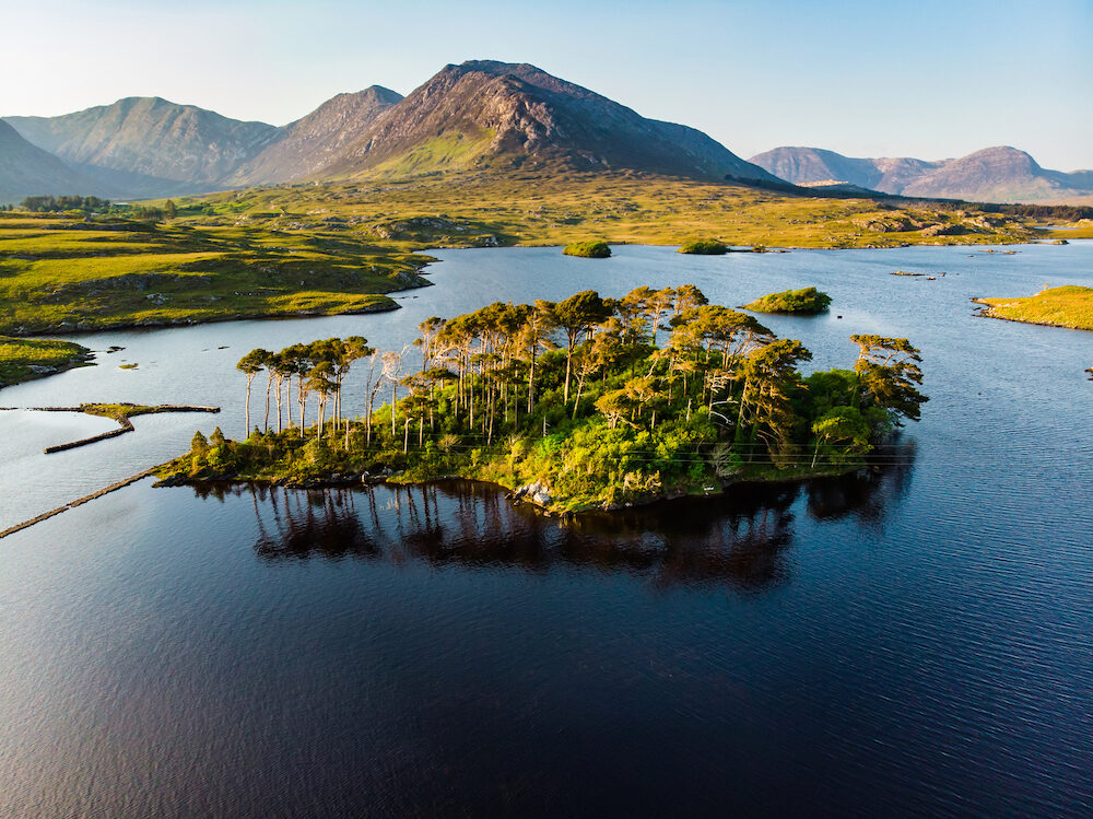 Aerial view of Twelve Pines Island, standing on a gorgeous background formed by the sharp peaks of a mountain range called Twelve Pins or Twelve Bens, Connemara, County Galway, Ireland