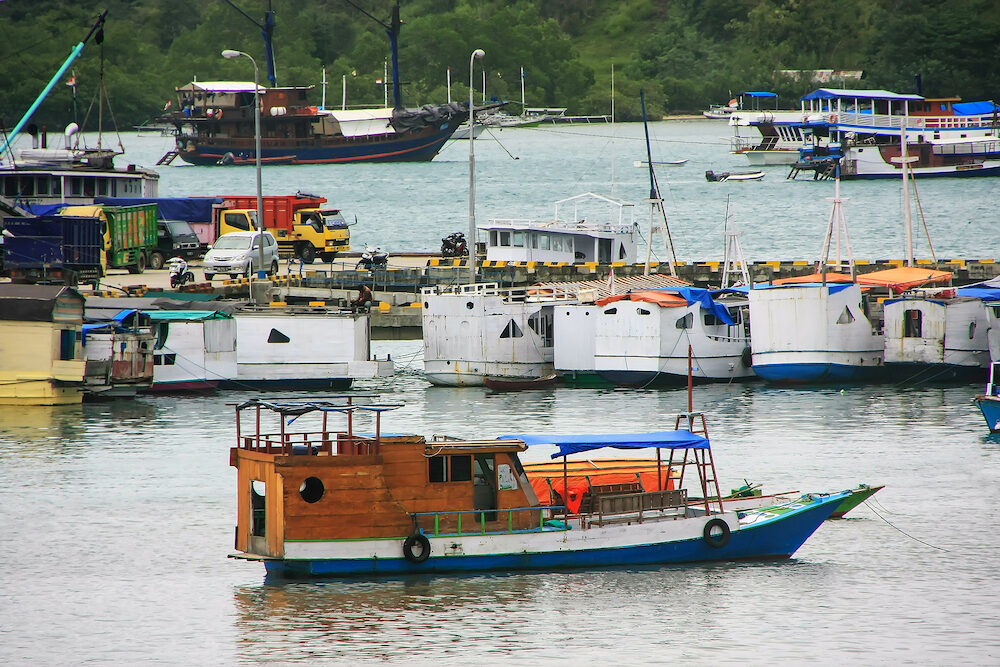 Boats anchored at Labuan Bajo town on Flores Island Nusa Tenggara Indonesia. The local economy in the town is centered around the ferry port and tourism.