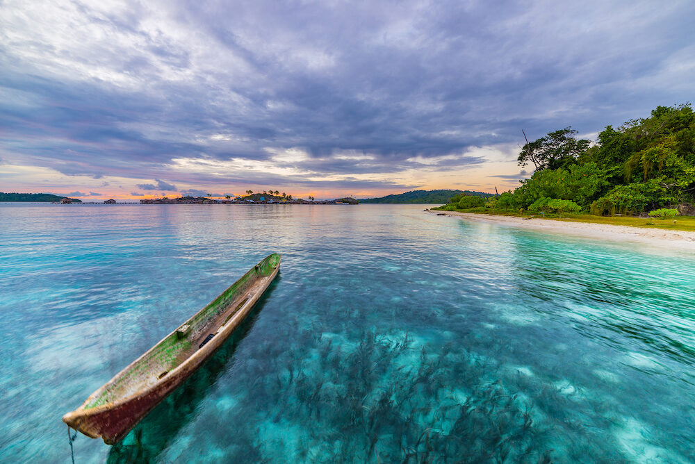 Tropical beach, caribbean sea, canoe floating on transparent turquoise water, remote Togean Islands (Togian Islands), Sulawesi, Indonesia. Dramatic sky at sunset.