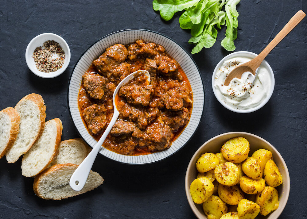 Irish beef stew and turmeric potatoes - delicious seasonal lunch on a dark background, top view. Flat lay. Comfort food