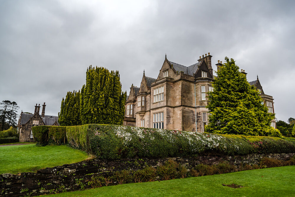 Killarney, Ireland - Muckross House and gardens against cloudy sky. It is a mansion designed in Tudor style, located in the The National Park of Killarney.