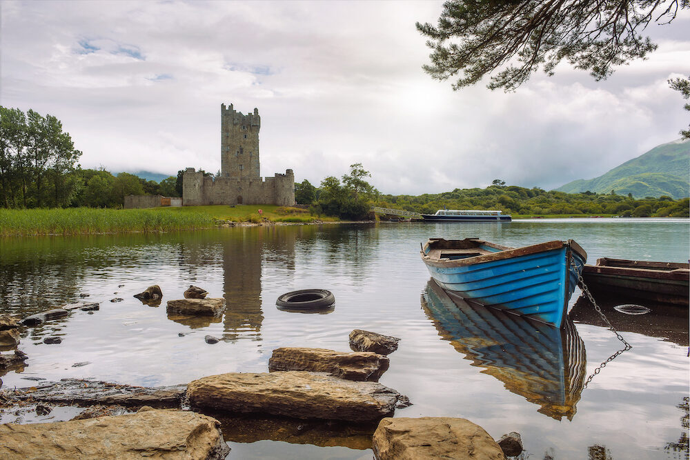 Ross Castle ruins and the Lough Leane lake with a blue boat in the foreground in the Killarney National Park, Ireland
