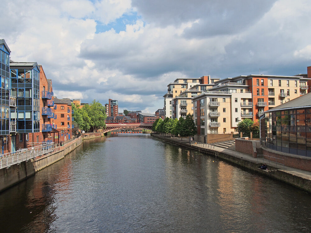 leeds, west yorkshire, united kingdom - a view along the river aire in leeds with waterside apartments and buildings with crown point bridge in the distance