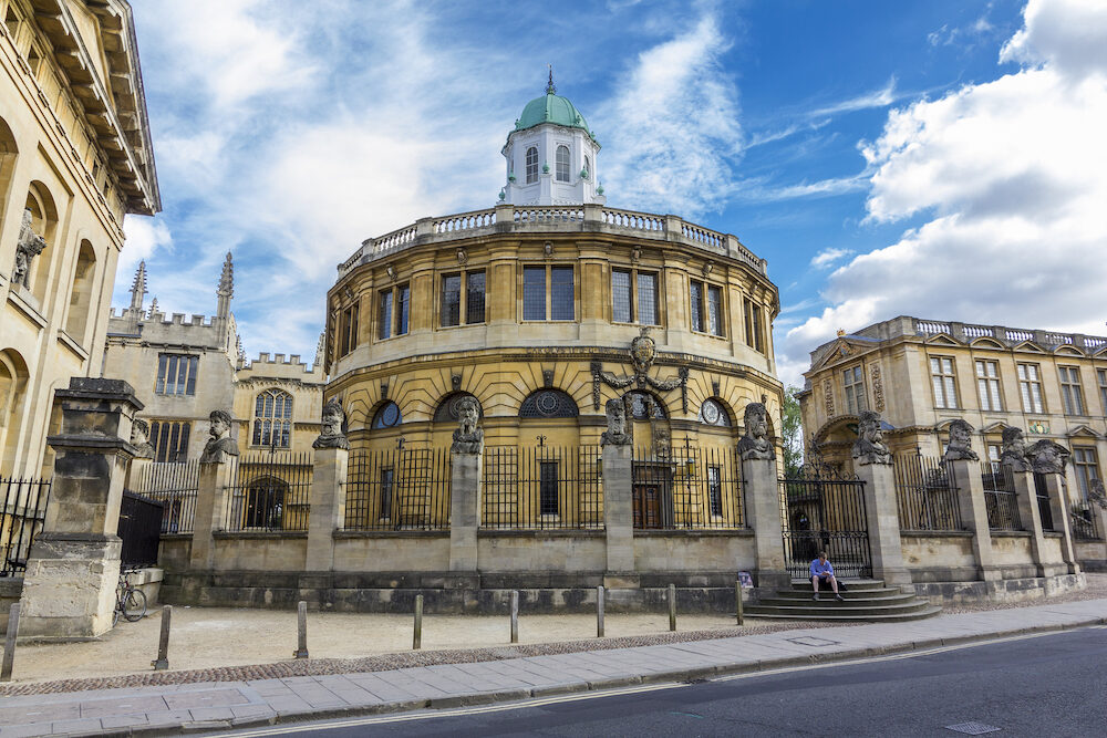Oxford England - A student sits on the stairs in front of the Sheldonian Theatre. Sheldonian theatre is one of the most important landmarks of Oxford.