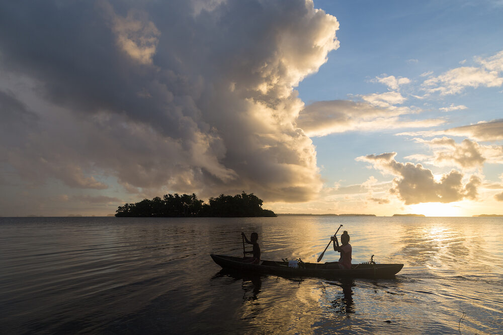 Marovo Lagoon, Solomon Islands - Children on the way to school with a canoe during sunrise