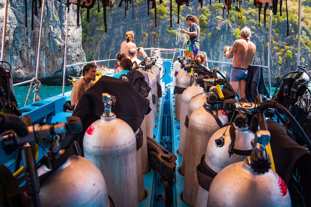 Phi Phi Island, Thailand - Group of scuba divers preparing for scuba diving on a boat full of scuba gear, Illustrative