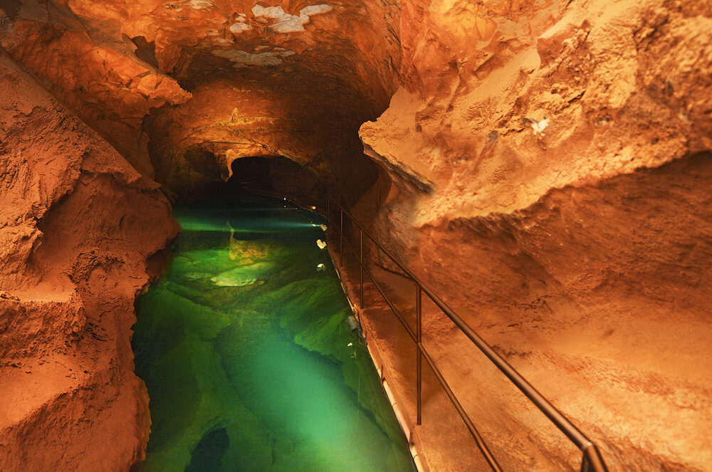 Woman looks at the water pool in River Cave at the Jenolan Caves at the Blue Mountains of New South Wales Australia.