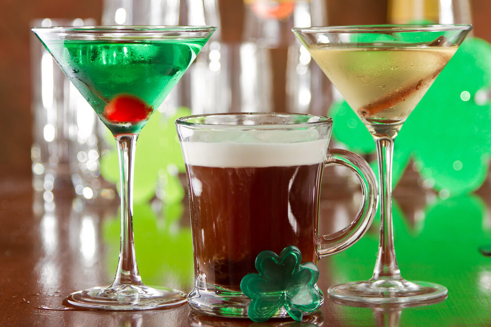 set up of some Irish drinks on a bar top with green shamrocks