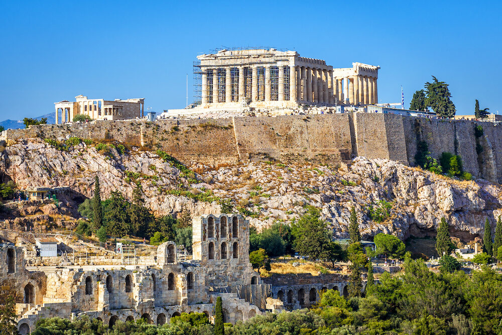Acropolis hill with Parthenon temple, Athens, Greece. Famous ancient Acropolis is a top landmark of Athens. Scenic view of Ancient Greek ruins in the Athens center. Remains of the antique Athens city.