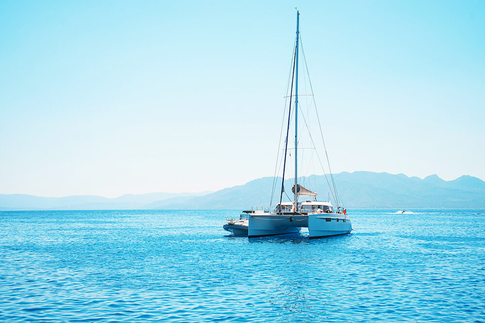 Sailing yacht catamaran boat in the sea in Greece, turquoise waters of Aegean Sea near Athens. Famous travel sailing destination in Europe. Sailboat.
