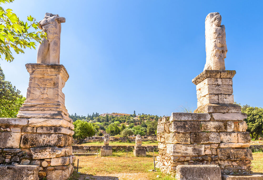 Statues on the ancient Agora, Athens, Greece. Scenic view of the historical park in Athens center. Famous old Greek Agora is one of the main landmarks of Athens. Remains of antique Athens in summer.