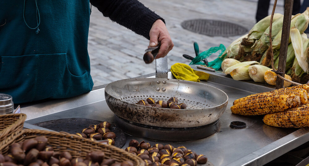 Street food. Roasting and selling sweet corns and chestnuts at Ermou street Athens, Greece.