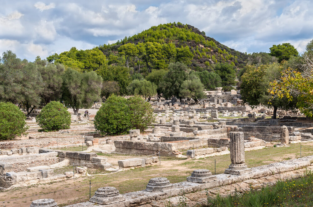 Olympia, Greece - Tourists visiting the ancient Olympia, Peloponnese, Greece. In antiquity the Olympic Games were hosted every four years in Olympia from 776 BC.