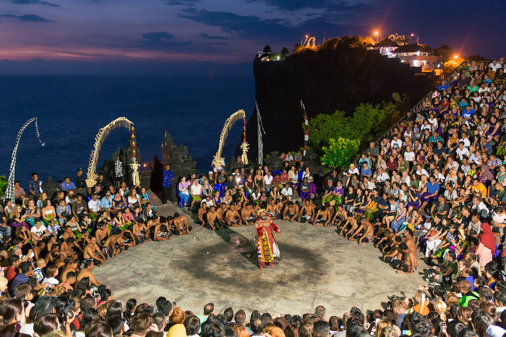 Bali, Indonesia - : Unidentified tourists watch traditional Balinese Kecak Dance at Uluwatu Temple on Bali, Indonesia. Kecak is very popular cultural show on Bali.