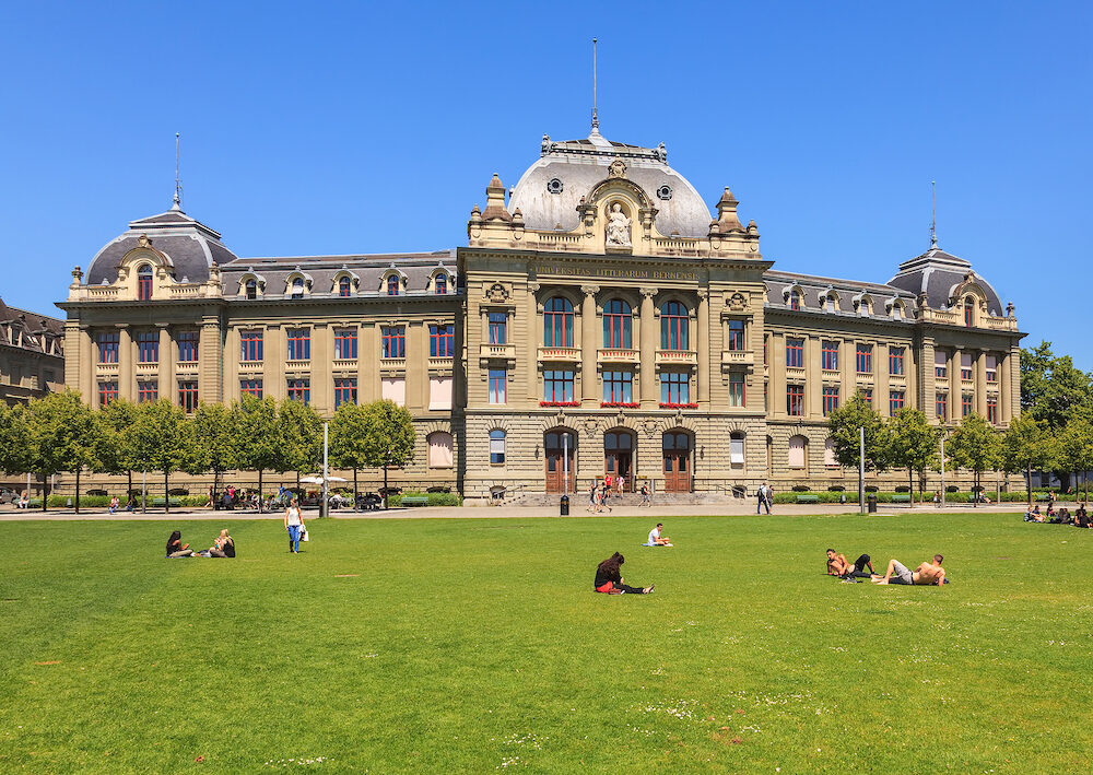 Bern, Switzerland - the main building of the University of Bern, people on the lawn in front of it. The University of Bern is a university in the Swiss city of Bern, founded in 1834.