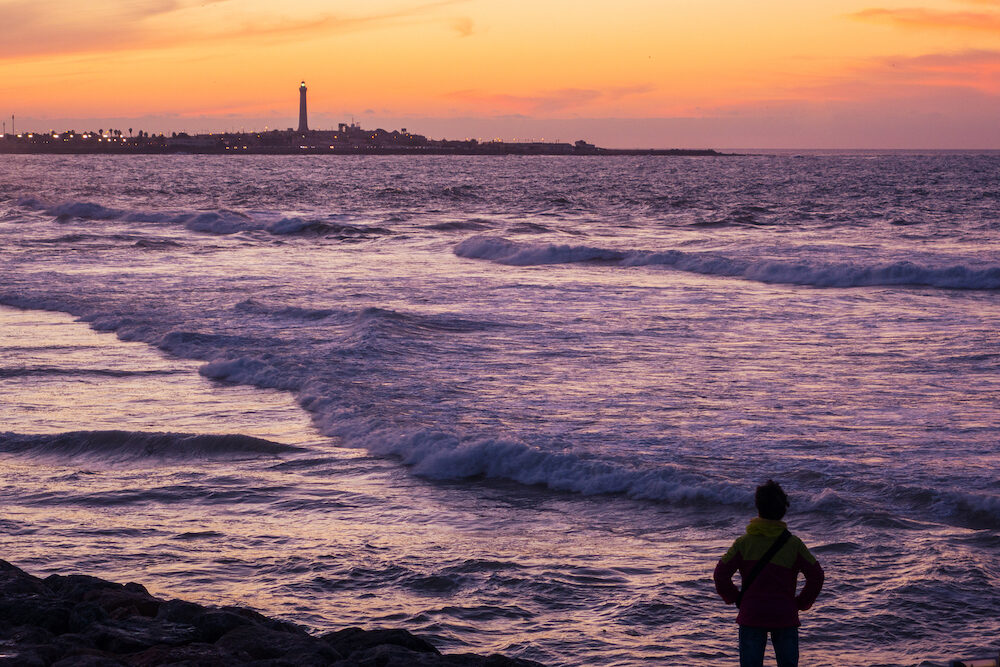 View from afar of the famous lighthouse and a tourist looking at it - Casablanca - Morocco