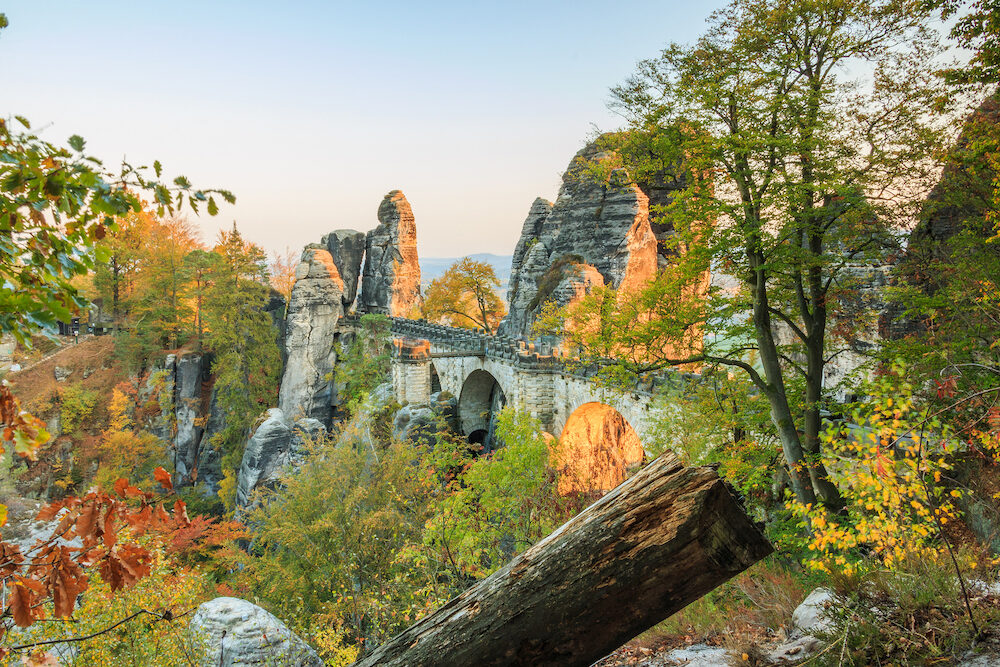 Bastei bridge in the evening sun in the national park Saxon Switzerland. Elbe sandstone mountains with trees in autumn colors and rock formations and old tree trunk in the foreground
