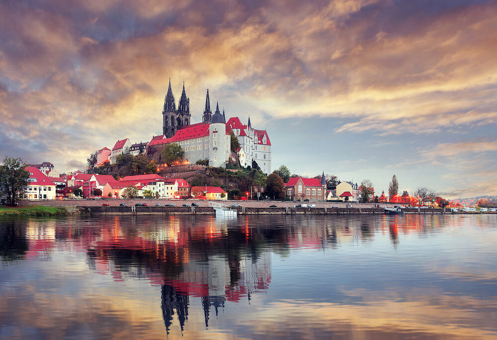 Unsurpassed Colorful Sunset. Wonderful View Albrechtsburg castle and cathedral on the River Elbe in Meissen during golden Hour, Saxony, Germany. Scenic image of townscape. Popular Places photorgaphy