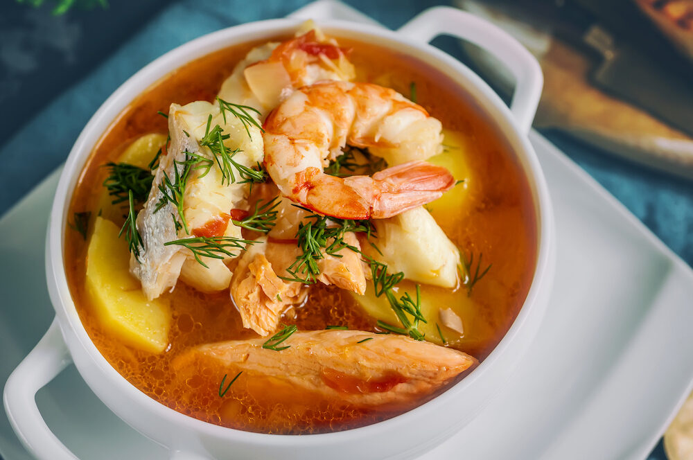French fish soup Bouillabaisse with seafood, salmon fillet, shrimp, rich flavor, delicious dinner in a white beautiful plate. Close up.