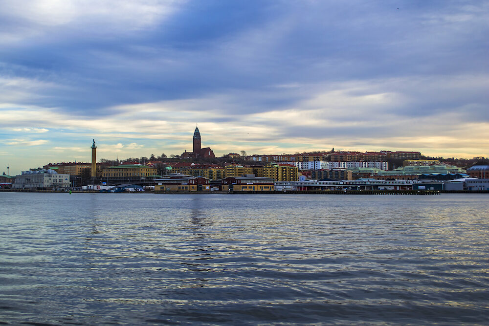 Gothenburg / Sweden - View across the river Gota Alv towards the districts of Masthugget and Majorna with the famous landmarks, the Masthugget Church (Masthuggskyrkan), and the statue the Seaman Tower, by the Maritime Museum and Aquarium.