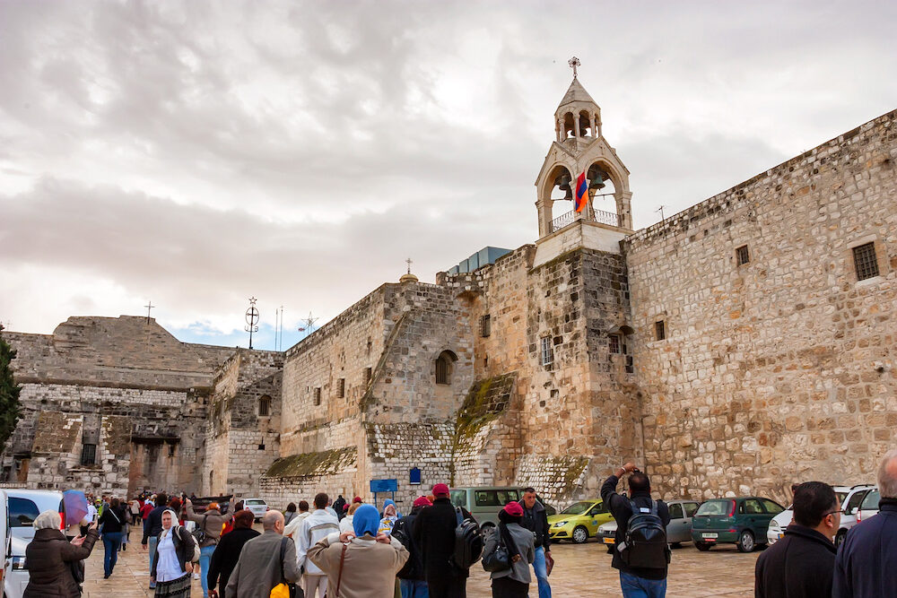BETHLEHEM, ISRAEL - Groups of people gather outside the Church of Nativity on cloudy day