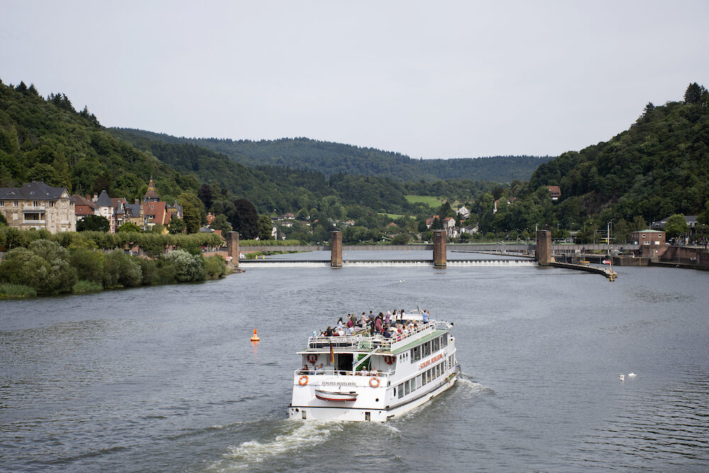 Cruises riding in Rhine and Neckar river bring passengers traveler visit and looking at riverside of Heidelberg old town in Heidelberg, Germany