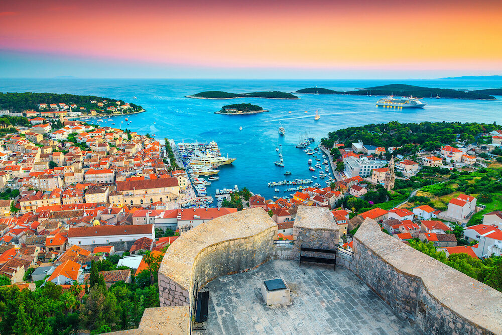 Famous touristic and travel destination. Picturesque view from the Tvrdava Fortica (Spanjola) fortress at sunset. Green islands, blue lagoons and fantastic harbor, Hvar town, Hvar island, Dalmatia, Croatia, Europe
