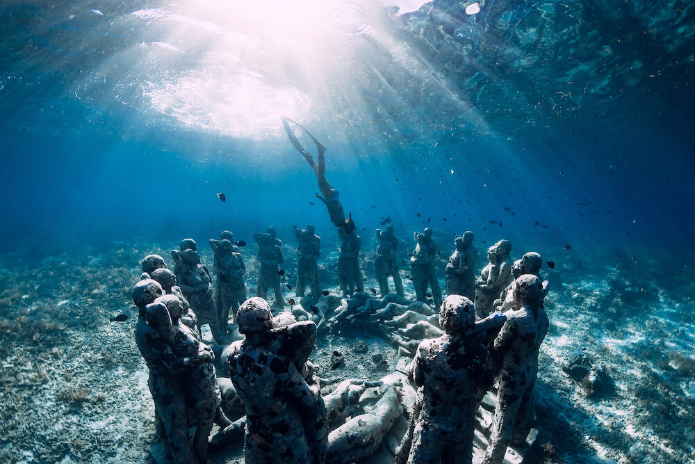 Gili Meno, Indonesia. Woman freediver with fins dive near underwater statues. Underwater tourism in the ocean.