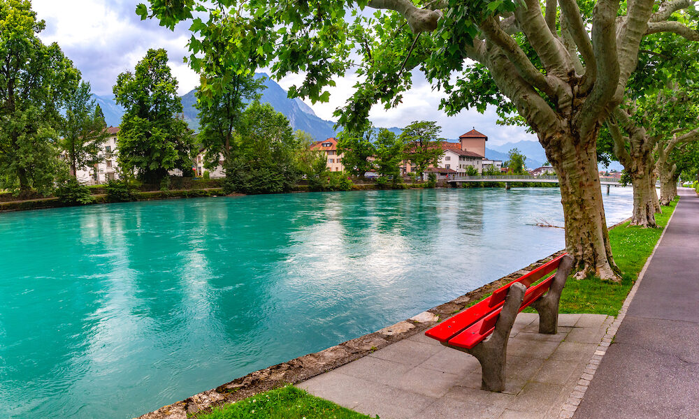 City park along the bank of Aare river in Old City of Interlaken, important tourist center in the Bernese Highlands, Switzerland.