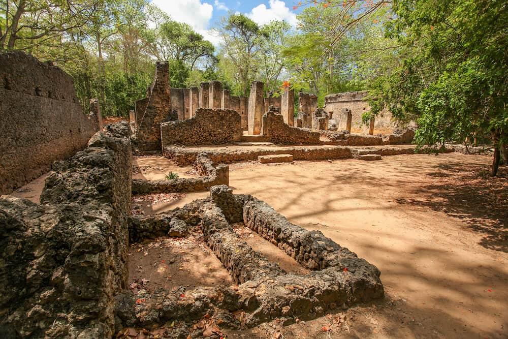 Ruins of ancient african city Gede (Gedi) in Watamu, Kenya with trees and sky in background.