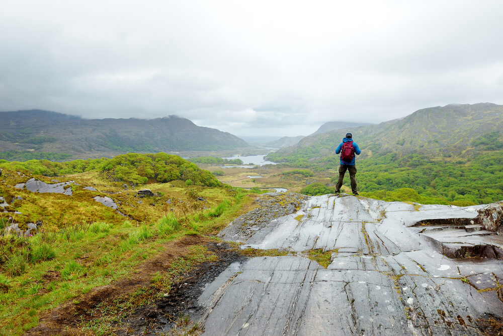 Male hiker admiring the beauty of Killarney National Park at Lady's View viewpoint. One of most impressive overlooks on the Ring of Kerry, Ireland.