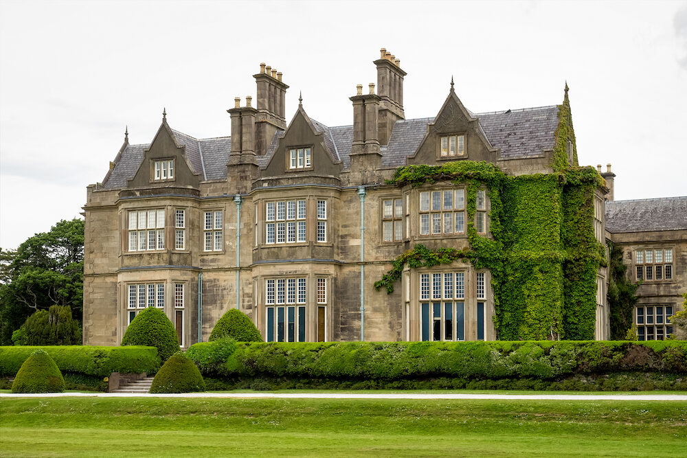 Muckross House and gardens against cloudy sky. It is a mansion designed in Tudor style, located in the The National Park of Killarney.