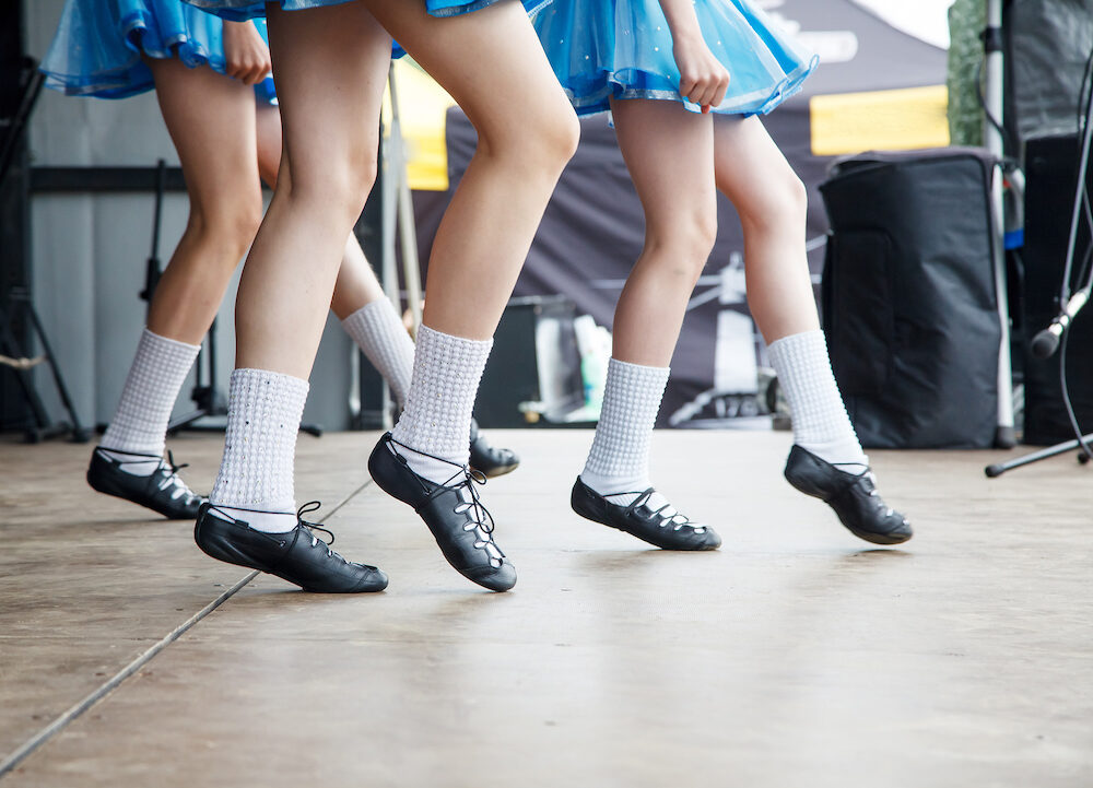 female legs of three irish dancers in blue dresses on the stage closeup