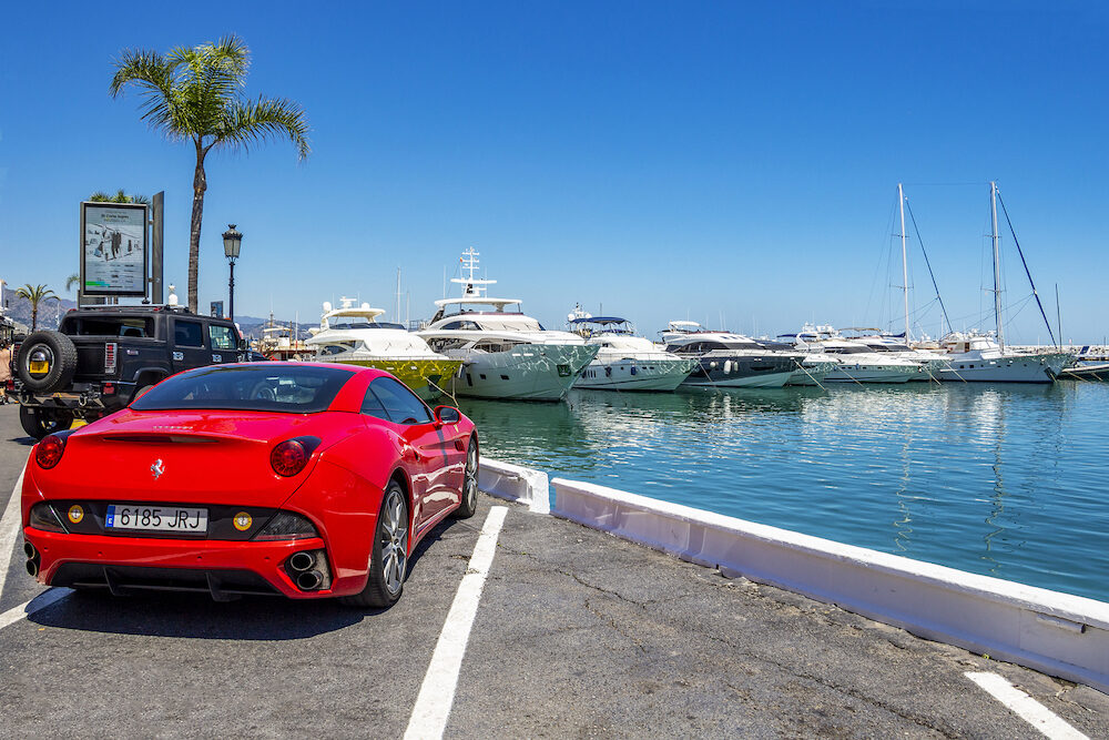 PUERTO BANUS, SPAIN - A red Ferrari California in front of luxury yachts at Puerto Banus, Nueva Andalucia, Marbella, Province of Malaga, Andalusia Spain