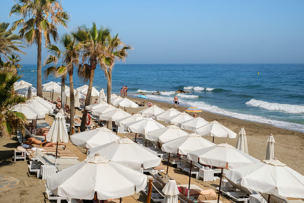 Marbella, Spain - People at the beach with palm trees on the shore of the Mediterranean Sea, Marbella city and resort area, province of Malaga, Andalucia region, Spain, Western Europe.
