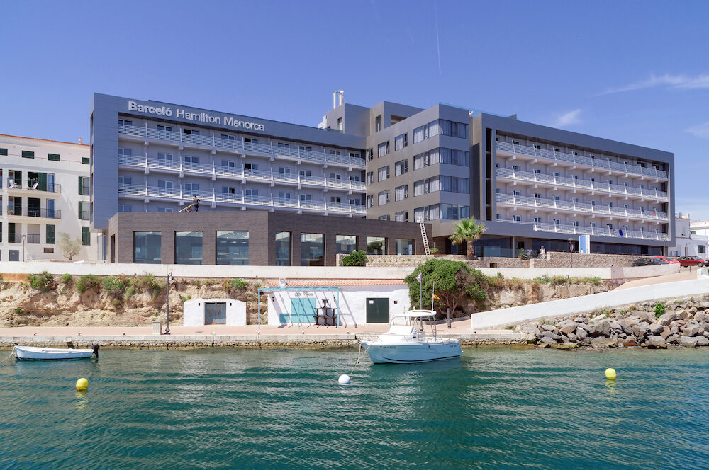 Mahon/Spain. The port of Mahon in Menorca on a warm summer's day. Port side luxury hotels enjoy prominent harbor views