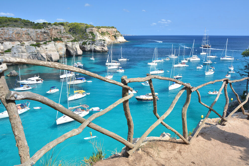 Turquoise water in bay Cala Macarella on Menorca island in Spain. Wooden typical fence.