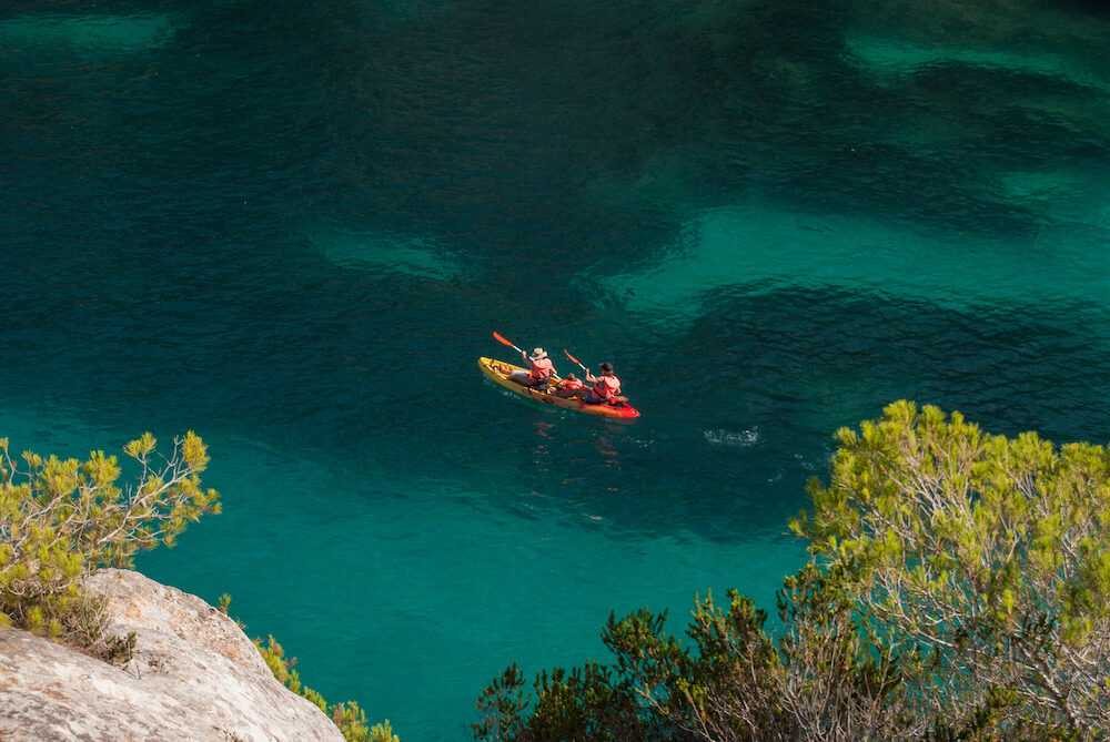 Two adults paddling with baby on board in the colorful Hawaiian sea of Menorca