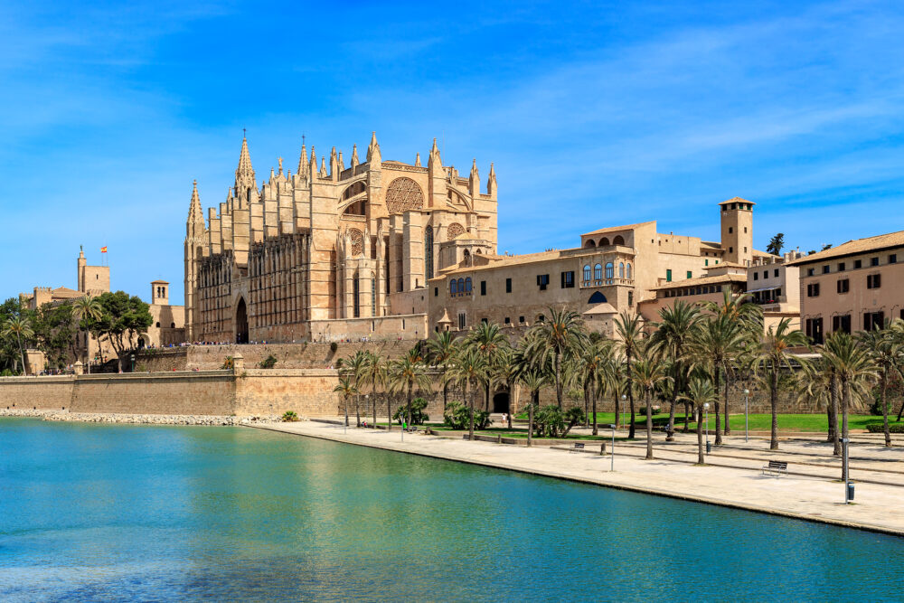 View of Parc de la Mar and famous Cathedral of Santa Maria under blues sky in Palma de Mallorca, Spain.