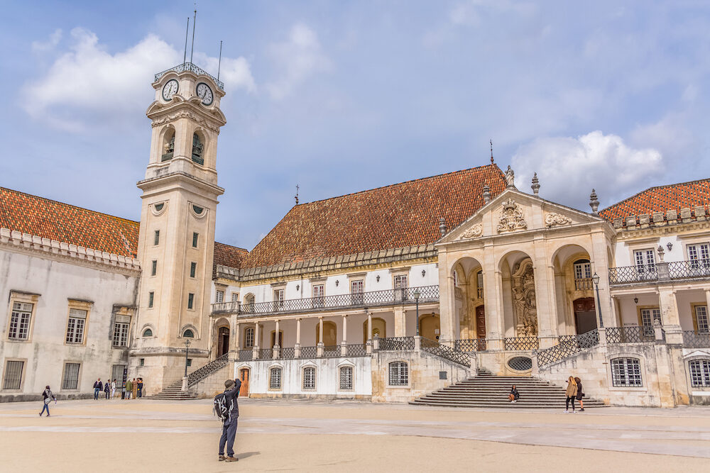 Coimbra / Portugal - View of the tower building of the University of Coimbra, classic architectural structure with masonr and other classic buildings around, tourists in scene, in Coimbra, Portugal