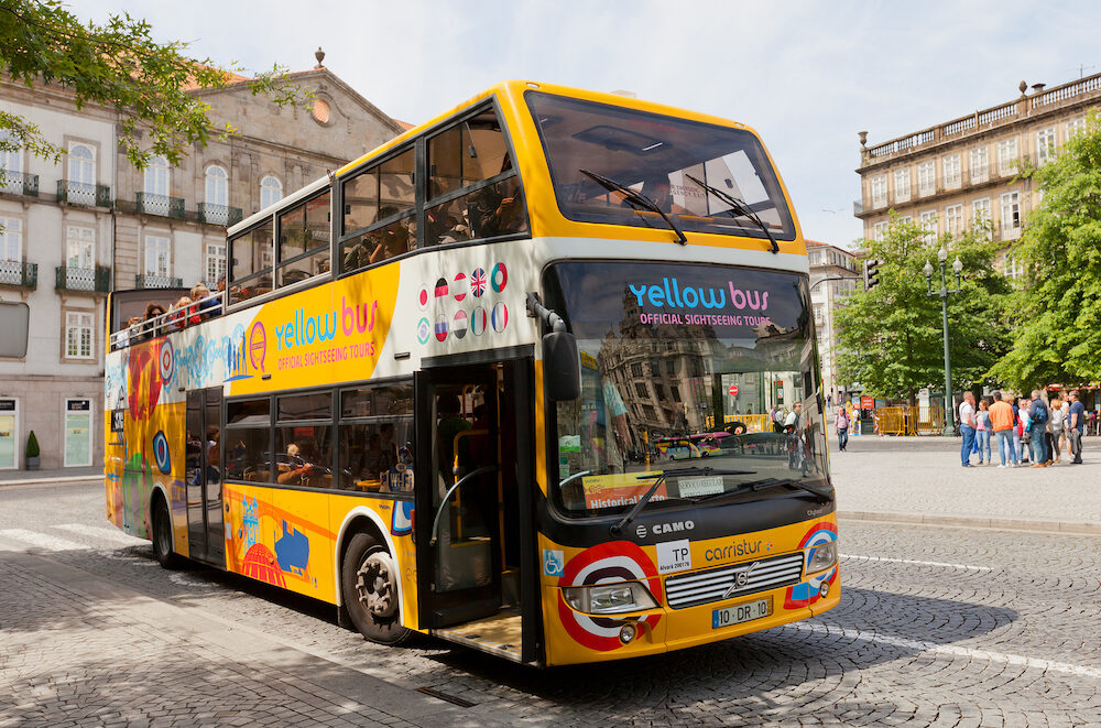 PORTO PORTUGAL - Yellow Bus on Liberdade Square in the historical center of Porto Portugal (UNESCO site). Yellow Bus provides two lines of city sightseeing tours around main attraction of the city and suburbs
